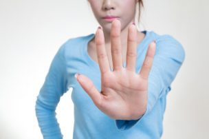 Asian women showing stop hand gesture, selective focus