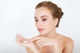 beauty, people, skincare and cosmetics concept - happy young woman with moisturizing cream on hand
