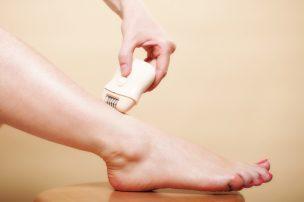 電気シェーバーで足を剃る女性